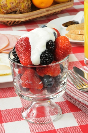A healthy breakfast with berries, canadian bacon, and eggs photo