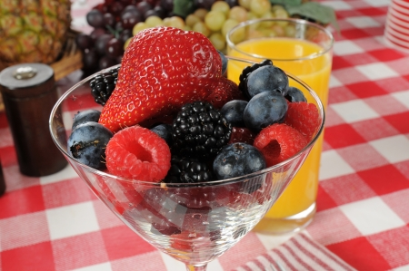 A martini glass with strawberries, blueberries, raspberries, and blackberries photo