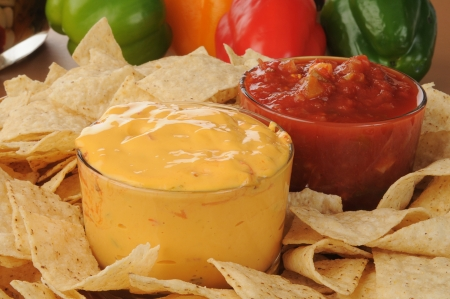 dipping: Close up of a tray of tortilla chips with salsa and cheese dip Stock Photo