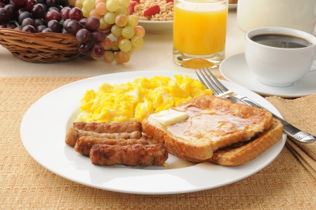 A healthy breakfast of french toast, sausage and scrambled eggs