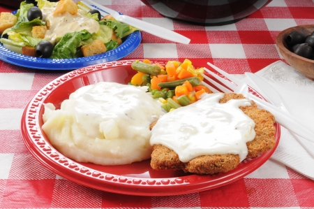 Chicken fried steak with mashed potatoes and country gravy on a picnic table photo