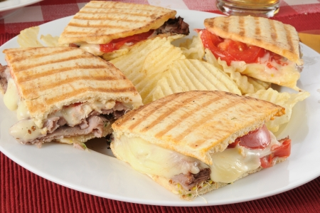 A roast beef panini sandwich with potato chips photo