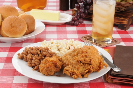 baked beans: A plate of fried chicken with Boston baked beans and rolls on a picnic table on a summer day