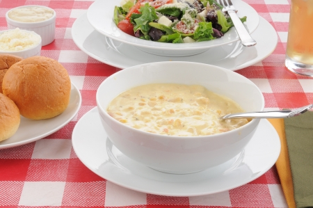 A bowl of hot corn chowder and a salad with dinner rolls Standard-Bild