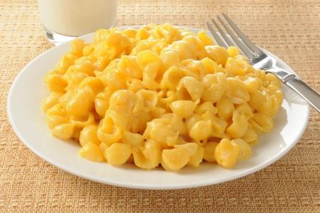 macarrones: Un plato de macarrones con queso con un vaso de leche Foto de archivo
