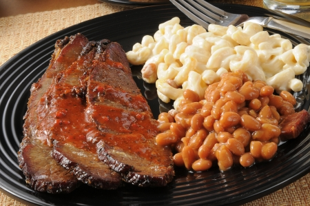 Closeup of beef brisket smoothered in barbecue sause with boston baked beans and macaroni salad
