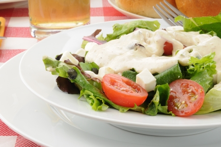 food dressing: Closeup of a tossed green salad with ranch dressing