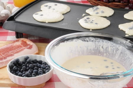 A bowl of blueberrry pancake batter with pancakes cooking on the griddle photo