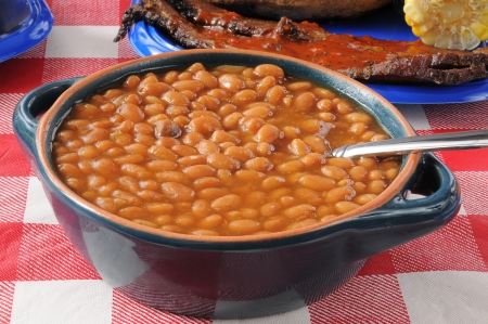 Closeup of a bowl of boston baked beans on a picnic table 스톡 콘텐츠