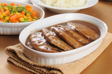A platter of salisbury steak with gravy and side dishes