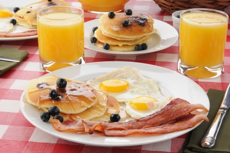 A breakfast with bacon and fried eggs with blueberry pancakes and orange juice