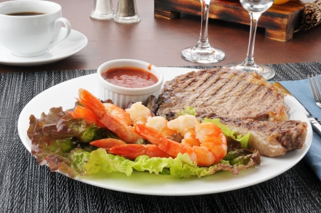 A grilled rib steak with tiger shrimp prawns photo