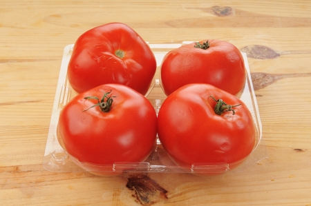 A plastic store container of fresh tomatoes on a cutting board photo