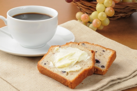 buttered: Two slices of buttered blueberry bread with a cup of coffee