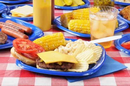 A cheeseburger on a picnic table loaded with food