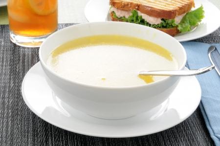 Een kom van chicken noodle soep met een broodje tonijn