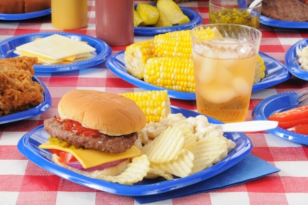 A cheeseburger with potato chips and corn on the cob on a picnic table loaded with food