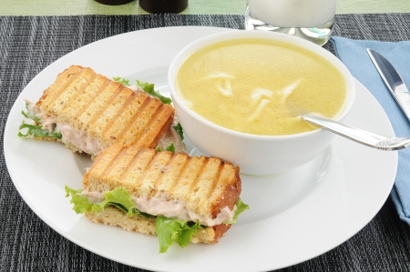 A grilled tuna sandwich with chicken noodle soup
