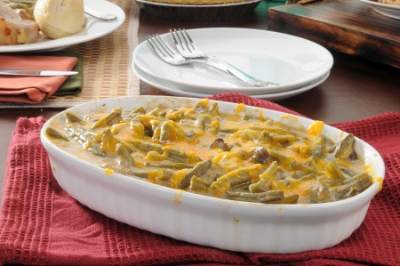A green bean casserole topped with cheddar cheese photo