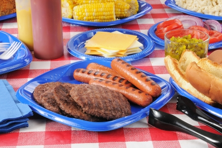 A picnic table with hamburgers, hot dogs, corn on the cob, and all the fixings Stock Photo