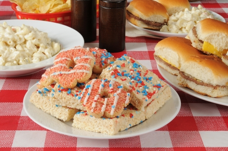 A plate of Independance Day cookies and dessert bars on a picnic table photo