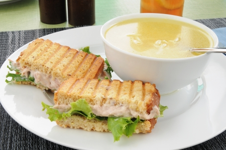 A grilled tuna sandwich and chicken noodle soup photo