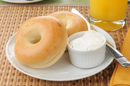 A plate of bagels with orange juice 스톡 콘텐츠