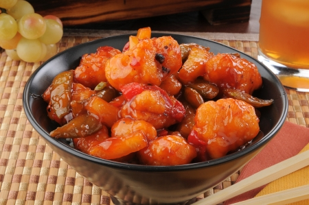 Closeup of a bowl of sweet and sour chicken with chop sticks