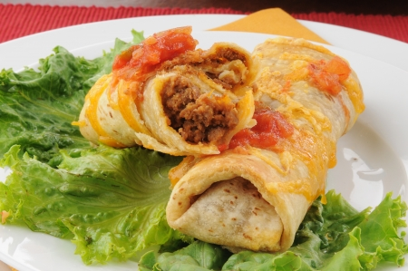 A close up of a broken open beef and bean chimichanga