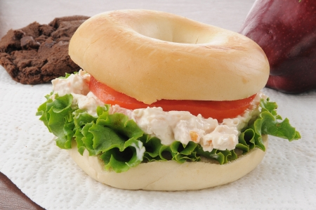 chicken salad bagel with cookies and an apple photo