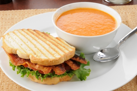 sandwich: A grilled bacon, lettuce tomato panini with tomato bisque soup