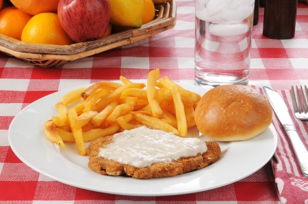 gravy: Chicken fried steak with fries and a basket of fruit Stock Photo