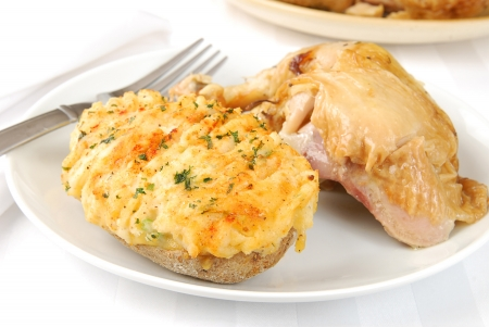 A baked chicken leg and a twice baked potato Stock Photo - 14464898