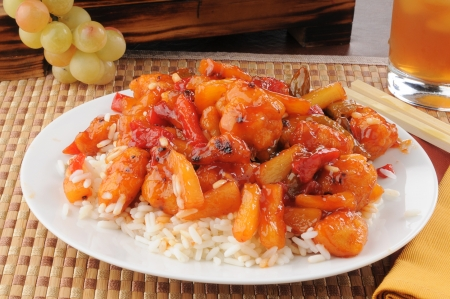 A closeup of a plate of sweet and sour chicken with chop sticks