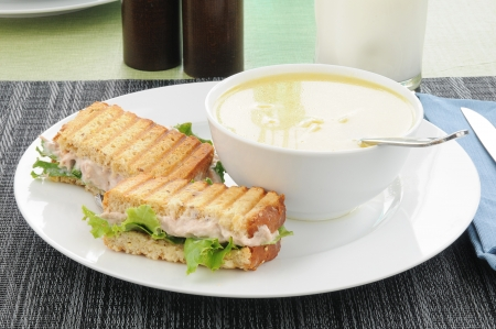 A grilled tuna sandwich with a glass of milk and chicken noodle soup photo