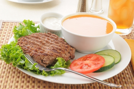 A healthy diet meal with a broiled hamburger patty, tomato, cucumber and soup photo