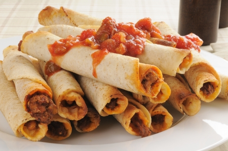 checker plate: A plate of taquitos topped with salsa Stock Photo