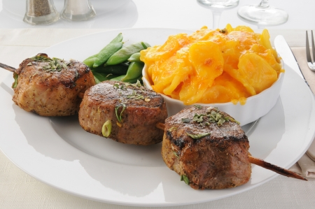 a skewer of pork tenderloins with au gratin potatoes and peas photo