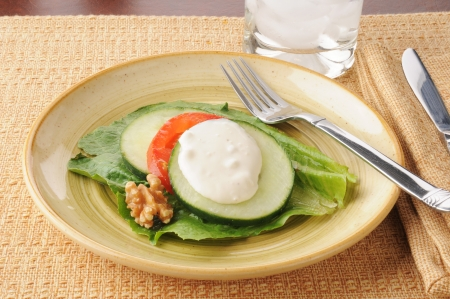 An extreme diet with lettuce, tomato, cucumber and a walnut
