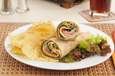 A plate of smoked turkey wraps with potato chips Stock Photo