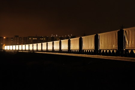 A freight train at night illuminated by the headlight of an oncoming train