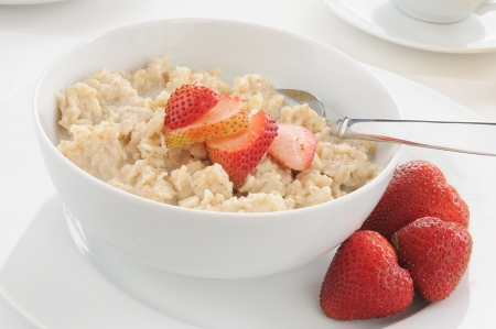 A bowl of oatmeal and strawberries with milk photo
