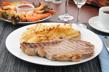 A grilled rib steak with waffle cut fries and shrimp Stock Photo - 14601694