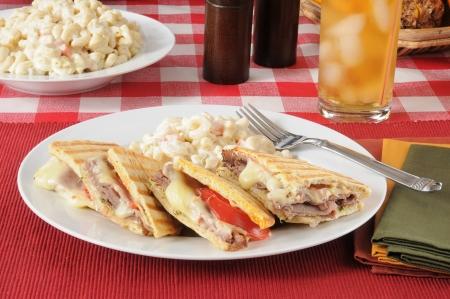 A roast beef and swiss cheese panini with macaroni salad photo