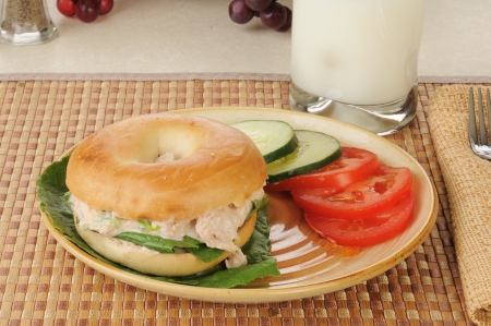 tunafish: A tunafish sandwich on a bagel with sliced tomato and cucumber