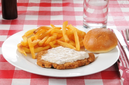 A chicken fried steak with french fries photo