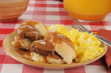A plate of sausage and biscuits with scrambled eggs and orange juice photo
