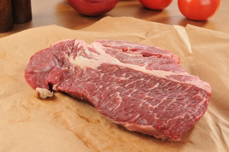 A raw chuck roast on brown wrapping paper