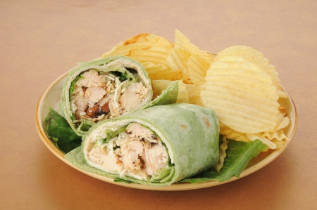 A plate of chicken caesar wraps with potato chips photo