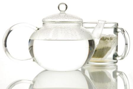 A cup of tea brews next to a pot